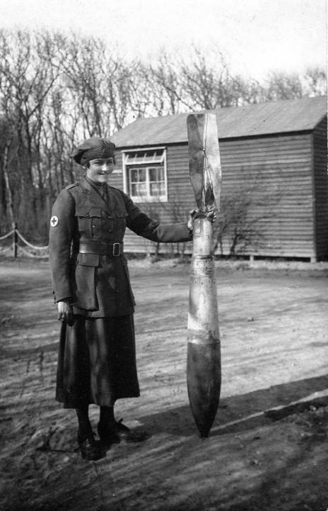 A First Aid Nursing Yeomanry driver with an unexploded German aerial bomb at a British hospital in Calais, 1918.